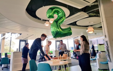 Roslin Innovation Centre celebrating 2 years of business with cake shared with tenants in the open-plan office